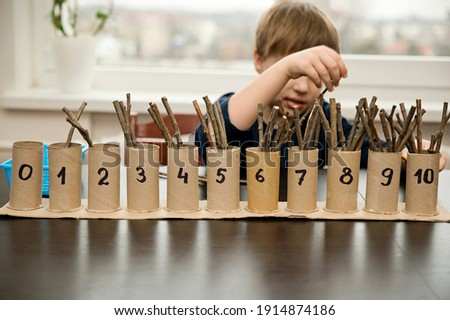 Little child doing simple math exercises. Early education, counting game. Preschool exercise for kids. Child learn to count to ten. Montessori math tool.  ストックフォト ©