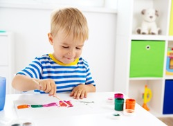 Little child drawing on the paper. Boy sitting on the chair at table with paints