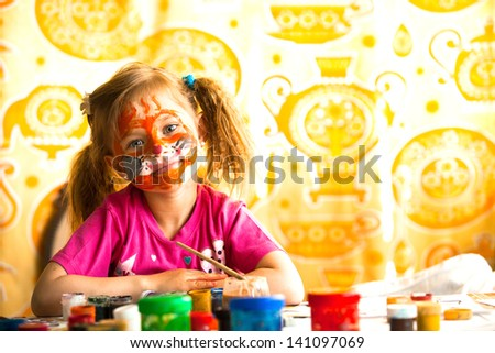 Little child drawing paint with paint of face.