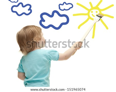 Little child drawing sun with a paintbrush
