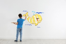 Little child drawing yellow whale on white wall indoors