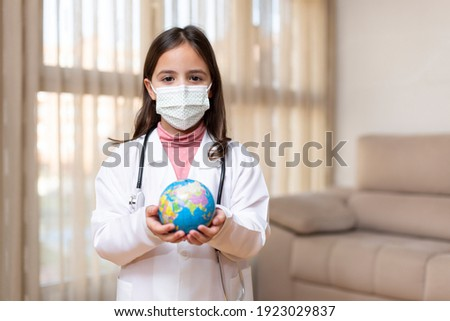 Little child dressed as a doctor with a medical mask holding a ball of the world in her hands. World Health Day concept. Space for text.