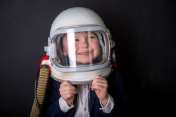 Little child dressed in astronaut helmet costume in empty room. Child autism.  Weird kid. Autistic kid go back to school.