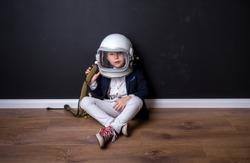 Little child dressed in astronaut helmet costume in empty room. Child autism.  Weird kid. Autistic kid go back to school. Lonely little child boy