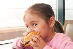 Little child eating a hamburger in the cafe