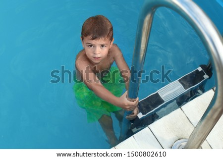 Little child getting out of outdoor swimming pool. Dangerous situation