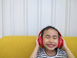 Little child girl enjoys while use red headphone listening to music. Online music streaming concept. Copyspace for text.