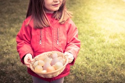Little child girl, face not visible, wearing red jacket, smiling and holding a basket of eggs. Easter, spring wallpaper or background with sun flare and copy space.