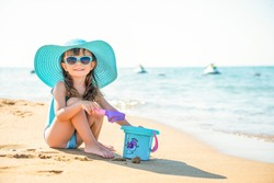 Little child girl fashionista in a blue wide-brimmed hat and sunglasses sits on the sand with a bucket on the seashore