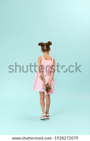 little child girl holding bouquet of roses behind her back on blue background. back view ストックフォト ©