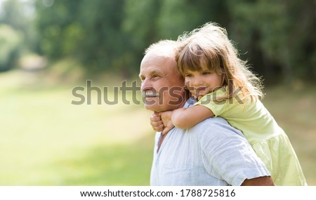 Little child girl hugs grandpa On Walk in the summer outdoors. Concept of friendly family.  Сток-фото ©
