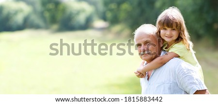 Little child girl hugs grandpa On Walk in the summer outdoors. Concept of friendly family. copy space. banner  Сток-фото ©