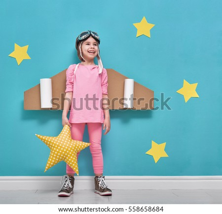 Little child girl in an astronaut costume is playing and dreaming of becoming a spaceman. Portrait of funny kid on a background of bright blue wall with yellow stars. #558658684