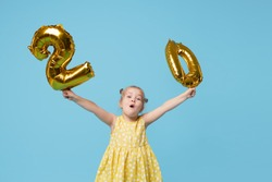 Little child girl is holding foil balloons in the form of numbers 20 twenty percent. The concept of discounts, sales and cashback. Blue studio background