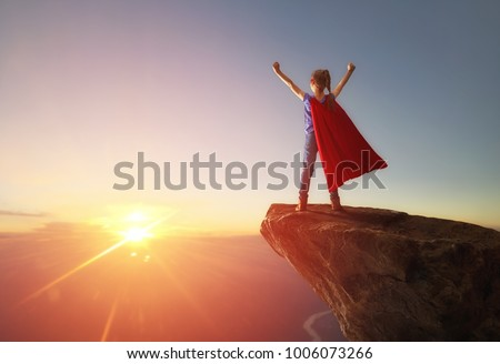 Little child girl is playing superhero. Child on the background of sunset sky. Girl power concept #1006073266