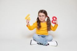 Little Child Girl Playing with Figures, early Education, Mathematics and Numeracy. Cute Girl with glasses sit legs crossed