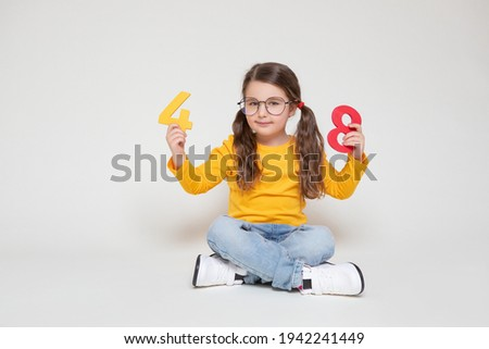Little Child Girl Playing with Figures, early Education, Mathematics and Numeracy. Cute Girl with glasses sit legs crossed                                         Foto stock ©