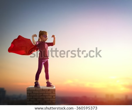 Little child girl plays superhero. Child on the background of sunset sky. Girl power concept