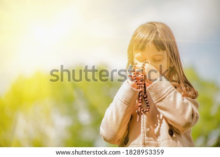 Little child girl praying with a sweet expression. She looks down and holding a wooden rosary. Selective focus on rosary. Stock photo ©