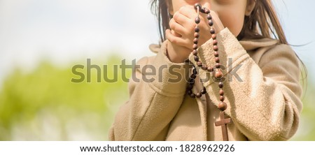 Little child girl praying with wooden rosary. Horizontal image. Stock photo ©