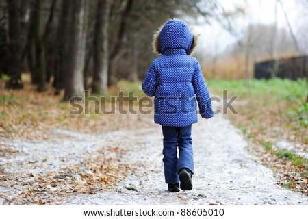 Little child girl walking along the road covered in first snow