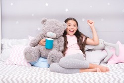 Little child hold mug. Girl in pajamas drinking tea. Relaxation before sleep. Drinking milk just before bed. Bedtime beverage. Hot milk before sleep. Health Benefits Drinking water before bed.