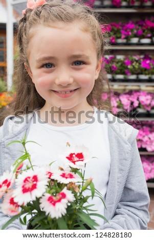 Little child holding a flower in garden center