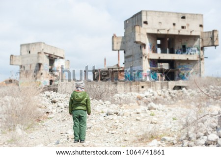 little child in jacket stands against ruins of building as result of war conflict Stockfoto ©