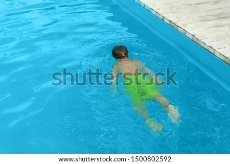 Little child in outdoor swimming pool. Dangerous situation