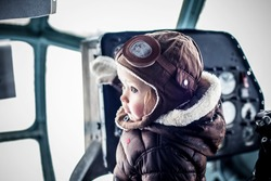 little child in the helicopter at the helm pilot cap