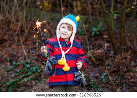 Little child in winter clothes holding burning sparkler on New Year\'s Eve. Safe fireworks for kids concept. Happy kid boy outdoors.