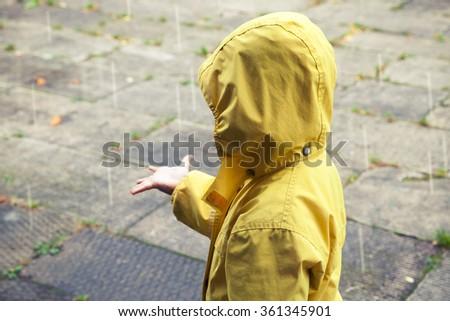 little child in yellow raincoat ...