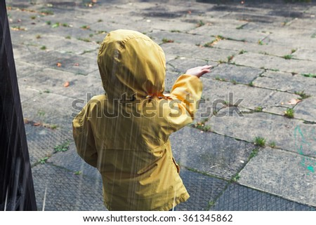 Little child in yellow raincoat playing with raindrops. Vintage tonal correction photo filter effect