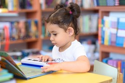 Little Child Indoors In Front Of Books. Cute Young Toddler Sitting On A Chair Near Table and play with toy piano. Kid in a bookstore, surrounded by colorful books. Happy multirace girl play the piano.