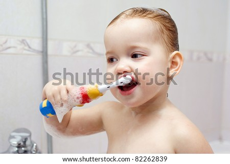 little child is brushing her teeth in bath