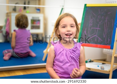 Little child is drawing with pieces of color chalk on the chalk board. Girl is expressing creativity and looking at the camera, smiling in a nursery, classroom or playroom. Concept of learning