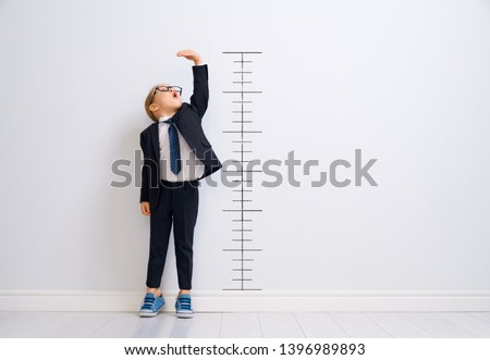 Photo of  Little child is playing businessman. Kid is measuring the growth on the background of wall. Smart power concept.