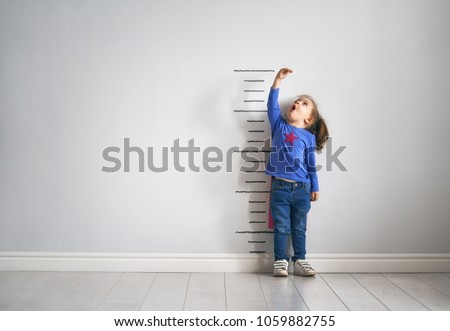 Photo of  Little child is playing superhero. Kid is measuring the growth on the background of wall. Girl power concept.