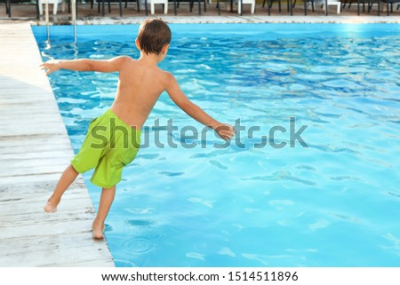 Little child jumping in outdoor swimming pool. Dangerous situation