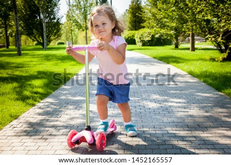 Little child learning to ride a scooter in a city park on sunny summer day. Active  healthy leisure and outdoor sport for kids. Fun activity for kid. toddler girl riding a scooter.