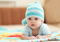 little child lying on a children's rug in the white-blue cap.  Small Depth of Field (DOF)