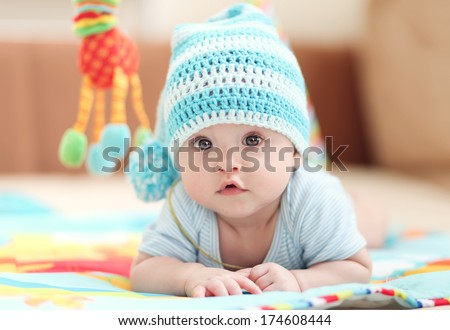 little child lying on a children's rug in the white-blue cap. Small Depth of Field (DOF)  #174608444