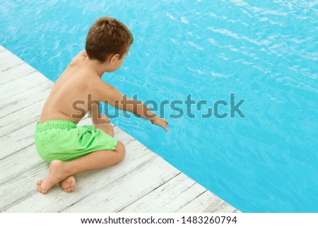 Little child near outdoor swimming pool. Dangerous situation #1483260794