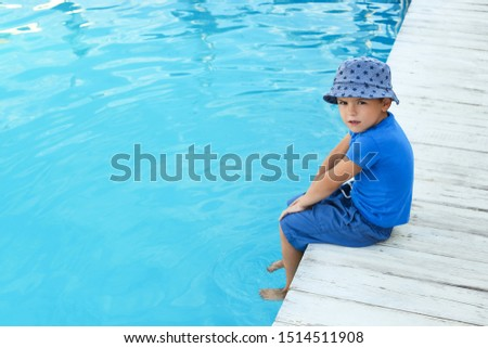 Little child near outdoor swimming pool. Dangerous situation