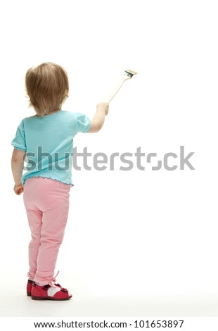 Little child painting white wall with a paintbrush, rear view full length portrait