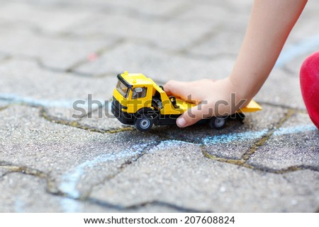 Little child playing with car toy. Selective focus on hand of boy and toy