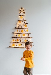 Little child playing with handmade craft Christmas tree made from sticks and natural materials hanging on wall. Sustainable Christmas, zero waste, plastic free, eco friendly.