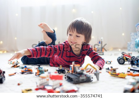 Shutterstock Little child playing with lots of colorful plastic toys indoor, building different cars and objects