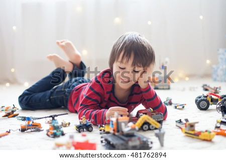 Little child playing with lots of colorful plastic toys indoor, building different cars and objects #481762894