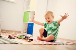 Little child playing with toy cars. Boy sitting on the floor at home